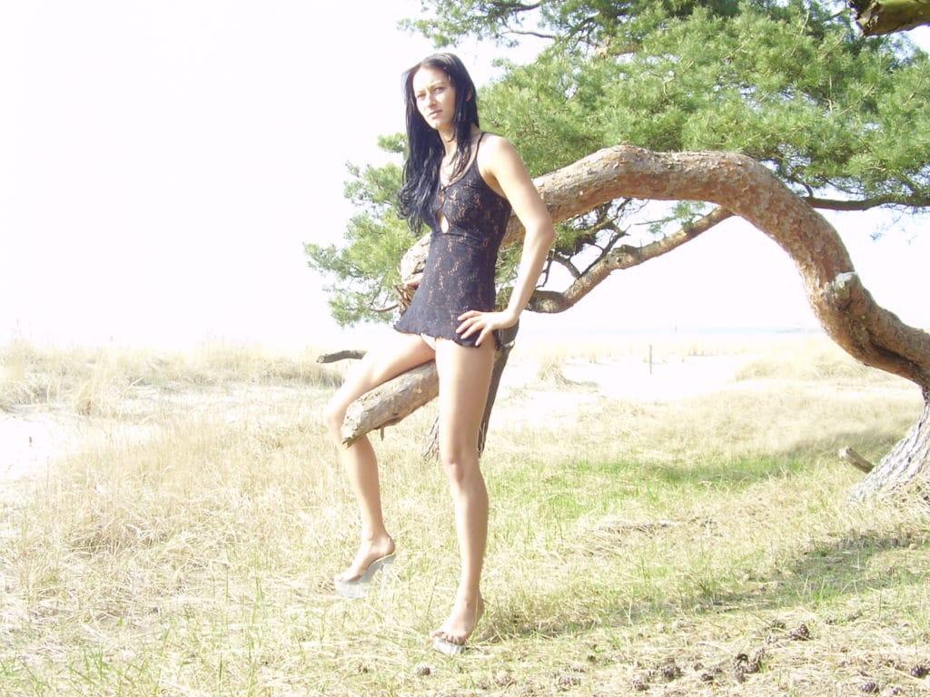 Schwarzhaarige sitzt nackt auf einem Ast